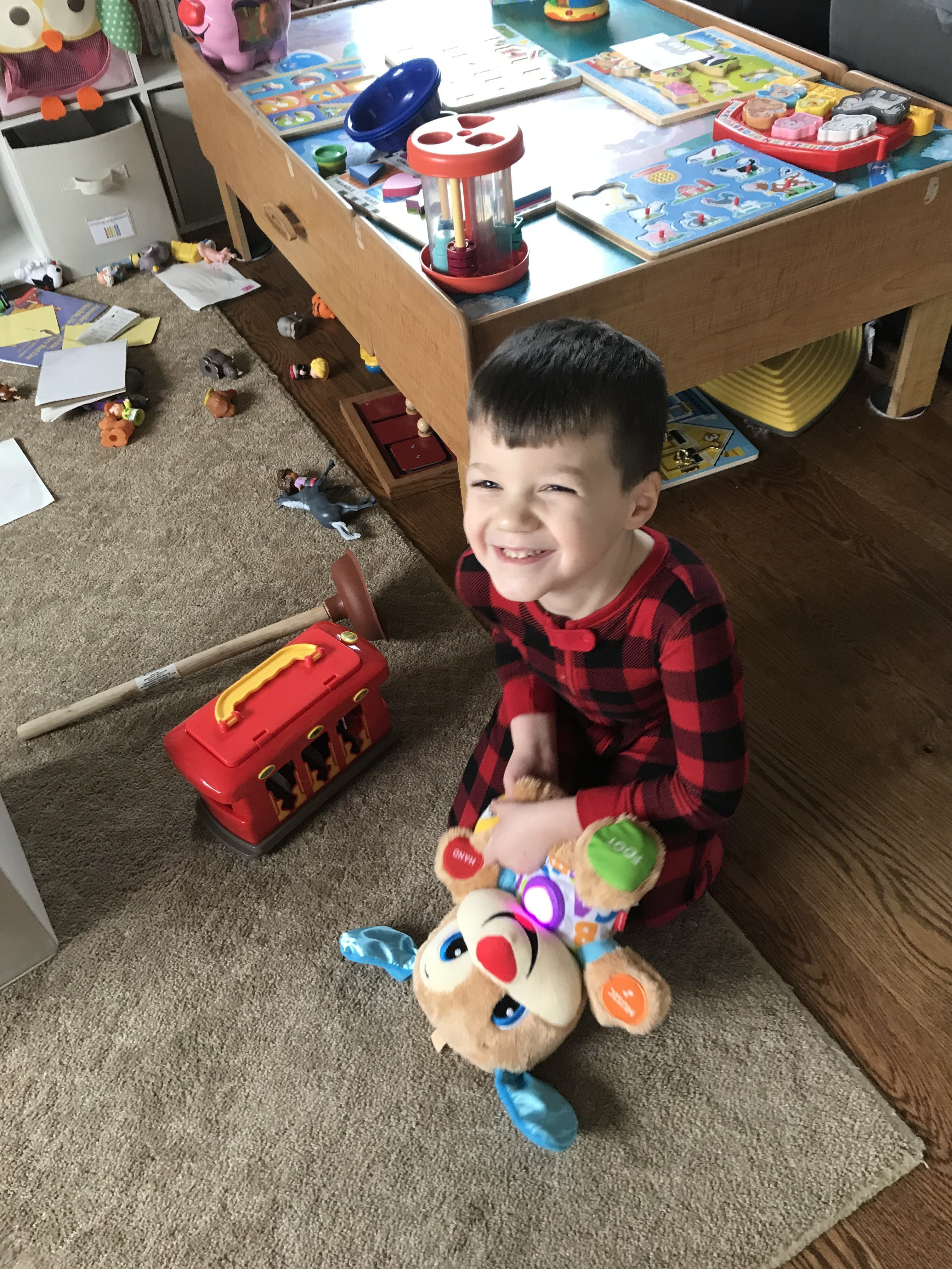 sad young boy shouting with toys scattered around, child in